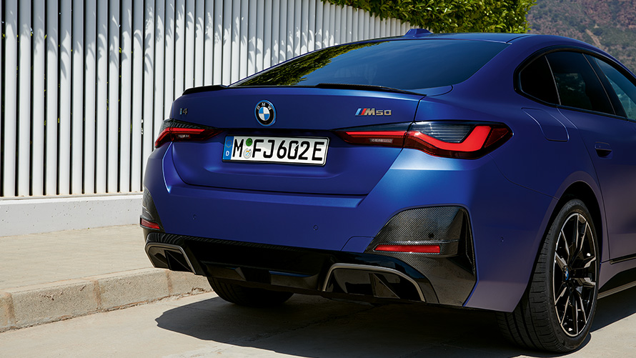 BMW i4 M50 G26 2021 BMW Individual Frozen Portimao Blau metallic Dreiviertel-Heckansicht stehend am weißen Zaun